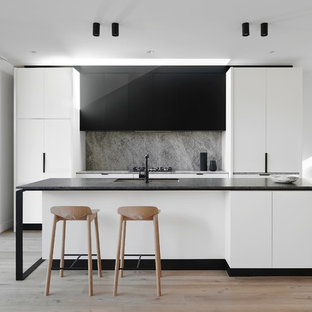 Inspiration for a contemporary galley open plan kitchen in Melbourne with an undermount sink, flat-panel cabinets, black cabinets, grey splashback, panelled appliances, light hardwood floors and with island.