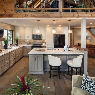 Inspiration for a mid-sized contemporary l-shaped dark wood floor and brown floor open concept kitchen remodel in San Luis Obispo with a single-bowl sink, recessed-panel cabinets, gray cabinets, quartz countertops, beige backsplash, ceramic backsplash, black appliances, an island and white countertops