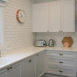 シドニーの大きいシャビーシック調のおしゃれなキッチン (一体型シンク、シェーカースタイル扉のキャビネット、白いキャビネット、白いキッチンパネル、シルバーの調理設備の、サブウェイタイルのキッチンパネル、塗装フローリング、黒い床、白いキッチンカウンター、人工大理石カウンター) の写真