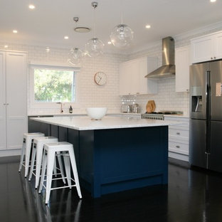 Design ideas for a large shabby-chic style l-shaped open plan kitchen in Sydney with an integrated sink, shaker cabinets, white cabinets, marble benchtops, white splashback, stainless steel appliances, with island, subway tile splashback, painted wood floors, black floor and white benchtop.
