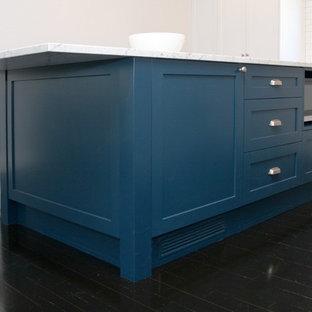 シドニーの大きいシャビーシック調のおしゃれなキッチン (一体型シンク、シェーカースタイル扉のキャビネット、大理石カウンター、白いキッチンパネル、シルバーの調理設備の、サブウェイタイルのキッチンパネル、塗装フローリング、黒い床、青いキャビネット、グレーのキッチンカウンター) の写真