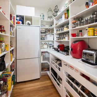 Foto di una grande cucina design con lavello sottopiano, ante bianche, elettrodomestici in acciaio inossidabile, pavimento in legno massello medio, pavimento marrone, nessun'anta, top in laminato, paraspruzzi bianco e isola