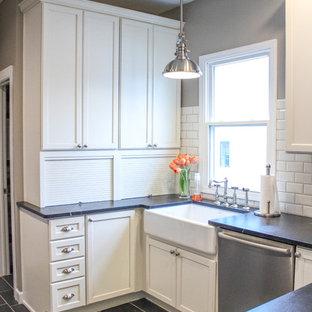 Foto på ett litet lantligt kök, med en rustik diskho, luckor med infälld panel, vita skåp, bänkskiva i täljsten, vitt stänkskydd, stänkskydd i tunnelbanekakel och rostfria vitvaror