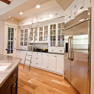 This is an example of a traditional kitchen in DC Metro with stainless steel benchtops, white cabinets and stainless steel appliances.