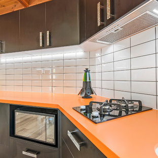 Design ideas for a small modern single-wall separate kitchen in Sunshine Coast with an integrated sink, solid surface benchtops, yellow splashback, subway tile splashback and orange benchtop.