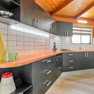Small modern single-wall separate kitchen in Sunshine Coast with an integrated sink, solid surface benchtops, yellow splashback, subway tile splashback and orange benchtop.