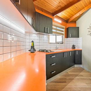 Foto di una piccola cucina lineare moderna chiusa con lavello integrato, top in superficie solida, paraspruzzi giallo, paraspruzzi con piastrelle diamantate e top arancione