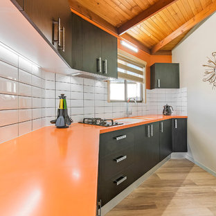 Inspiration for a small modern single-wall separate kitchen in Sunshine Coast with an integrated sink, solid surface benchtops, yellow splashback, subway tile splashback and orange benchtop.