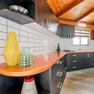 Photo of a small modern single-wall separate kitchen in Sunshine Coast with an integrated sink, solid surface benchtops, yellow splashback, subway tile splashback and orange benchtop.