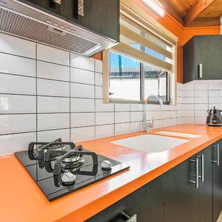 Foto de cocina lineal, moderna, pequeña, cerrada, con fregadero integrado, encimera de acrílico, salpicadero amarillo, salpicadero de azulejos tipo metro y encimeras naranjas