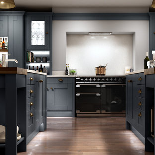 This is an example of a large farmhouse single-wall open plan kitchen in Other with a built-in sink, shaker cabinets, blue cabinets, quartz worktops, white splashback, black appliances, dark hardwood flooring, multiple islands and brown floors.