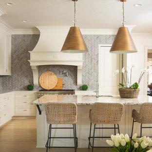 Inredning av ett lantligt beige beige l-kök, med en undermonterad diskho, luckor med infälld panel, vita skåp, grått stänkskydd, stänkskydd i mosaik, rostfria vitvaror, mellanmörkt trägolv, en köksö och brunt golv