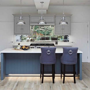 This is an example of a traditional u-shaped kitchen in London with shaker cabinets, blue cabinets, mirror splashback, an island and beige floors.