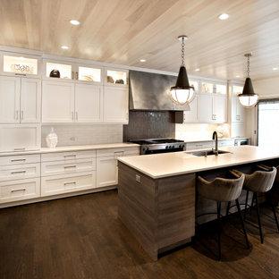 На фото: кухня в современном стиле с белыми фасадами, столешницей из кварцита, разноцветным фартуком, фартуком из кирпича, техникой из нержавеющей стали, островом, коричневым полом, белой столешницей и деревянным потолком с