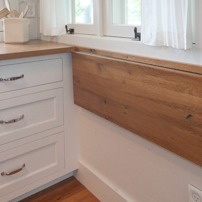 Inspiration for a coastal galley kitchen remodel in Other with shaker cabinets, white cabinets and wood countertops