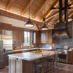 Diseño de cocina en L, industrial, con fregadero bajoencimera, armarios estilo shaker, puertas de armario de madera clara, salpicadero verde, electrodomésticos de acero inoxidable, una isla y encimeras blancas