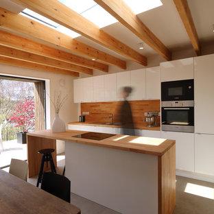 グロスタシャーの小さいカントリー風おしゃれなキッチン (ダブルシンク、フラットパネル扉のキャビネット、白いキャビネット、木材カウンター、シルバーの調理設備、コンクリートの床) の写真