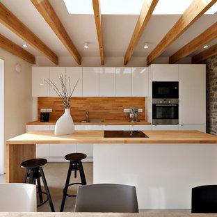 Offene, Zweizeilige, Mittelgroße Moderne Küche mit Doppelwaschbecken, flächenbündigen Schrankfronten, weißen Schränken, Arbeitsplatte aus Holz, Küchengeräten aus Edelstahl, Betonboden und Halbinsel in Gloucestershire