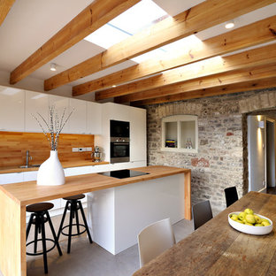 Inspiration for a mid-sized contemporary single-wall eat-in kitchen in Gloucestershire with a double-bowl sink, flat-panel cabinets, white cabinets, wood benchtops, stainless steel appliances, concrete floors and a peninsula.