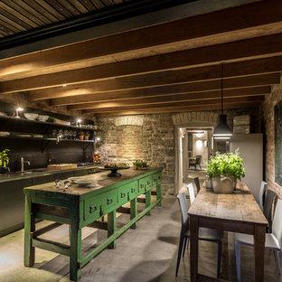 他の地域の小さいカントリー風おしゃれなキッチン (一体型シンク、フラットパネル扉のキャビネット、黒いキャビネット、木材カウンター、黒いキッチンパネル、黒い調理設備、コンクリートの床) の写真