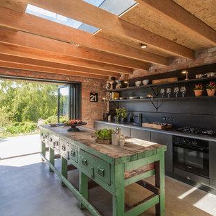 Inredning av ett lantligt mellanstort kök, med svarta skåp, svart stänkskydd, svarta vitvaror, betonggolv, en köksö och öppna hyllor