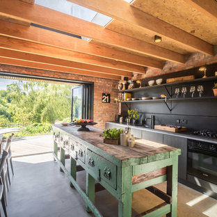 Mid-sized farmhouse eat-in kitchen photos - Example of a mid-sized country single-wall concrete floor and gray floor eat-in kitchen design in Other with an undermount sink, open cabinets, black cabinets, black backsplash, black appliances and an island
