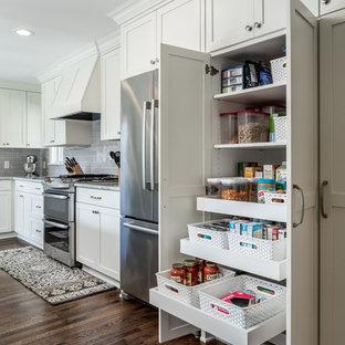 ミネアポリスの中くらいのトラディショナルスタイルのおしゃれなキッチン (アンダーカウンターシンク、シェーカースタイル扉のキャビネット、白いキャビネット、御影石カウンター、グレーのキッチンパネル、サブウェイタイルのキッチンパネル、シルバーの調理設備、濃色無垢フローリング) の写真