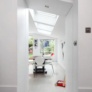 Inspiration för mellanstora moderna linjära vitt kök med öppen planlösning, med en integrerad diskho, släta luckor, vita skåp, bänkskiva i koppar, grått stänkskydd, stänkskydd i keramik, integrerade vitvaror, klinkergolv i keramik, en köksö och grått golv