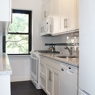 This is an example of a small contemporary galley separate kitchen in New York with an undermount sink, shaker cabinets, white cabinets, quartzite benchtops, white splashback, ceramic splashback, white appliances and porcelain floors.