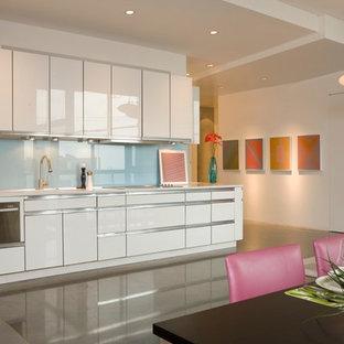 Foto de cocina lineal, minimalista, con electrodomésticos de acero inoxidable, armarios con paneles lisos, puertas de armario blancas, salpicadero azul y salpicadero de vidrio templado