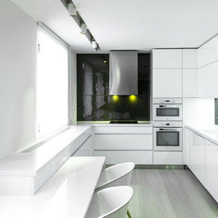 Photo of a medium sized modern u-shaped kitchen/diner in Other with an integrated sink, flat-panel cabinets, white cabinets, granite worktops, grey splashback, glass sheet splashback, white appliances, plywood flooring and a breakfast bar.
