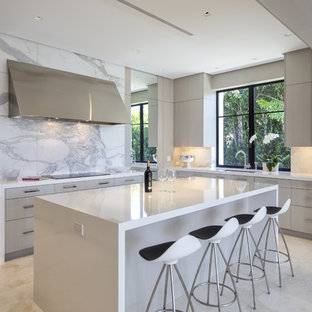 This is an example of a mid-sized contemporary open plan kitchen in Miami with an undermount sink, flat-panel cabinets, light wood cabinets, laminate benchtops, white splashback, stone slab splashback, marble floors, with island and stainless steel appliances.