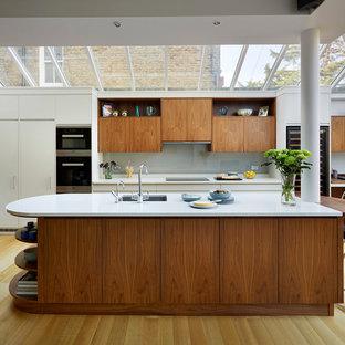 Foto de cocina actual, extra grande, abierta, con salpicadero verde, una isla, armarios con paneles lisos y encimera de cuarcita