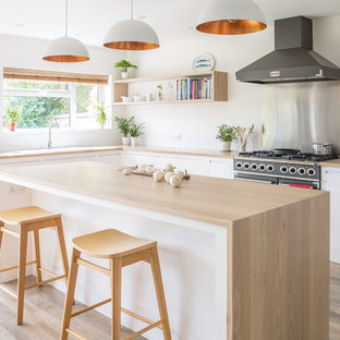 Photo of a large scandinavian l-shaped open plan kitchen in Other with a double-bowl sink, flat-panel cabinets, white cabinets, wood benchtops, white splashback, porcelain splashback, light hardwood floors and with island.