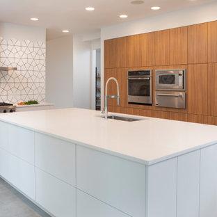 ニューヨークの広いコンテンポラリースタイルのおしゃれなキッチン (ドロップインシンク、フラットパネル扉のキャビネット、白いキャビネット、クオーツストーンカウンター、黄色いキッチンパネル、モザイクタイルのキッチンパネル、シルバーの調理設備、無垢フローリング、茶色い床、白いキッチンカウンター) の写真