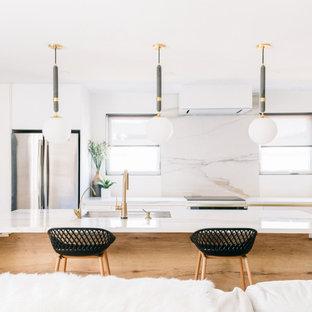 Exempel på ett litet modernt vit vitt kök och matrum, med en undermonterad diskho, släta luckor, skåp i ljust trä, kaklad bänkskiva, vitt stänkskydd, stänkskydd i porslinskakel, rostfria vitvaror, ljust trägolv, en köksö och beiget golv