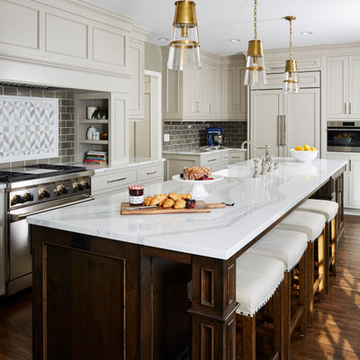 Kitchen - traditional l-shaped dark wood floor and brown floor kitchen idea in Minneapolis with a farmhouse sink, recessed-panel cabinets, gray cabinets, gray backsplash, subway tile backsplash, stainless steel appliances, an island and white countertops