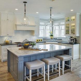 Große Landhaus Wohnküche in L-Form mit Landhausspüle, weißen Schränken, Küchenrückwand in Weiß, braunem Holzboden, Kücheninsel, Schrankfronten mit vertiefter Füllung, Marmor-Arbeitsplatte, Rückwand aus Keramikfliesen und Elektrogeräten mit Frontblende in Minneapolis