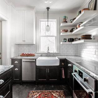 Modelo de cocina tradicional, pequeña, cerrada, con puertas de armario negras, encimera de granito, salpicadero de azulejos tipo metro, electrodomésticos de acero inoxidable, suelo de linóleo, suelo negro, fregadero sobremueble, armarios estilo shaker, salpicadero blanco y encimeras grises