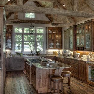 Idéer för rustika u-kök, med en rustik diskho, luckor med glaspanel, skåp i mellenmörkt trä, mellanmörkt trägolv och en köksö