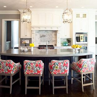 Источник вдохновения для домашнего уюта: кухня в классическом стиле с белыми фасадами, фартуком из каменной плитки, разноцветным фартуком, фасадами с утопленной филенкой, техникой из нержавеющей стали, темным паркетным полом и островом