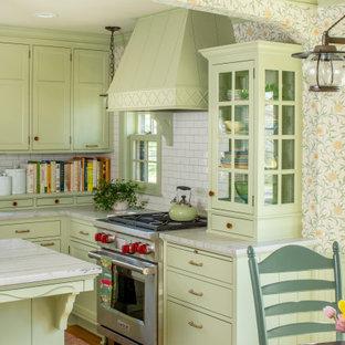 ミネアポリスのトラディショナルスタイルのおしゃれなキッチン (エプロンフロントシンク、落し込みパネル扉のキャビネット、緑のキャビネット、白いキッチンパネル、サブウェイタイルのキッチンパネル、シルバーの調理設備の、無垢フローリング、茶色い床、白いキッチンカウンター) の写真