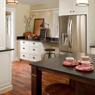 Große Klassische Küche in L-Form mit Vorratsschrank, Unterbauwaschbecken, Schrankfronten im Shaker-Stil, weißen Schränken, Granit-Arbeitsplatte, Küchenrückwand in Blau, Rückwand aus Metrofliesen, Küchengeräten aus Edelstahl, dunklem Holzboden und Kücheninsel in Minneapolis