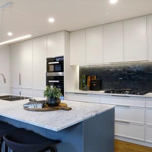 Пример оригинального дизайна: параллельная кухня-гостиная среднего размера в современном стиле с накладной раковиной, мраморной столешницей, фартуком из керамической плитки, техникой из нержавеющей стали, островом, белой столешницей, плоскими фасадами, белыми фасадами, черным фартуком, паркетным полом среднего тона и коричневым полом