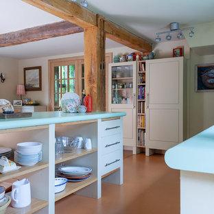 他の地域の中サイズのエクレクティックスタイルのおしゃれなキッチン (フラットパネル扉のキャビネット、白いキャビネット、ラミネートカウンター、シルバーの調理設備の、オレンジの床、緑のキッチンカウンター) の写真