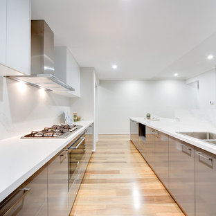 Contemporary l-shaped open plan kitchen in Perth with a double-bowl sink, flat-panel cabinets, grey cabinets, white splashback, stainless steel appliances, light hardwood floors and an island.