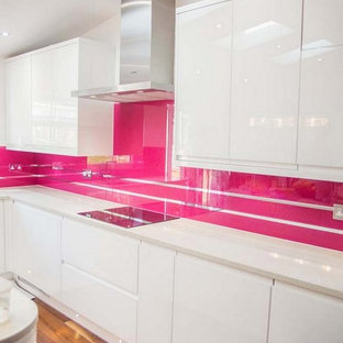Modern kitchen in Hertfordshire with pink splashback and glass sheet splashback.