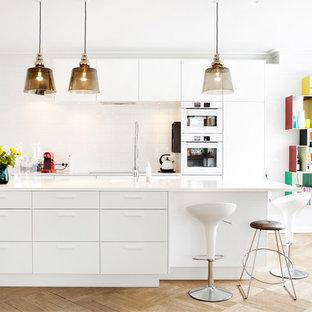 Modelo de cocina comedor de galera, actual, grande, con armarios con paneles lisos, puertas de armario blancas, salpicadero blanco, electrodomésticos blancos, suelo de madera clara, una isla, fregadero encastrado, encimera de vidrio reciclado y salpicadero de azulejos de porcelana