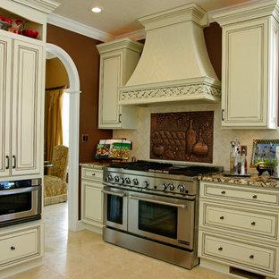 他の地域の中サイズのカントリー風おしゃれなキッチン (アンダーカウンターシンク、レイズドパネル扉のキャビネット、ヴィンテージ仕上げキャビネット、御影石カウンター、ベージュキッチンパネル、セラミックタイルのキッチンパネル、シルバーの調理設備の、セラミックタイルの床、ベージュの床) の写真
