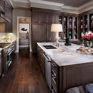 Large transitional u-shaped dark wood floor and brown floor eat-in kitchen photo in Las Vegas with a double-bowl sink, dark wood cabinets, white backsplash, stainless steel appliances, marble countertops, stone slab backsplash, an island and recessed-panel cabinets